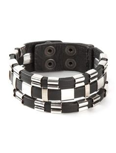'Black and silver buffalo leather and brass adjustable bracelet from Isabel Marant featuring silver-tone hardware and a top snap closure.'