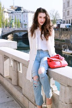 Fashion blogger Veronika Lipar of Brunette From Wall Street sharing how to wear light blue ripped jeans, hot pink bag and white shoes with long thin trench coat for a casual sexy spring look