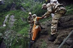 Indian army soldiers help a stranded elderly woman climb down a mountain in Govindghat, India, June 23, 2013. posted by floodlist.com