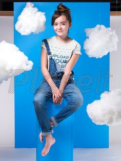 c443849a36 Girl Wearing a T-Shirt Mockup Standing Against a Blue Cardboard with Clouds  Hanging a19579Foreground
