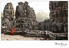 A novice monk looks up at the stone faces looking down at him - Bayon, Cambodia