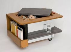 Type A Coffee Table -- it does it all: keeps drinks out of the way so you can rest your feet without knocking them over, organizes books and magazines, stores tons of junk out of sight and can even transform into a race car.... Plans available to build this yourself.