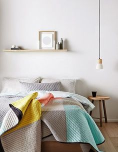 A pendant luminaire in this bedroom completes the simple and Scandinavian inspired look. Great wooden elements and a colorful blanket with a simple pattern.  Click to see more photos!