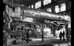 January 1936 - Passenger Engine No. 7856 of the Union Pacific rolled into the Los Angeles shops for a new set of tires. As simple as jacking up a flivver to put on the spare, workmen at the shops lifted the 200-ton locomotive from its wheels. August C. Roepke, mechanical supervisor, second from right, signals crane operator while J.H. Sinnar, foreman of the shop, extreme right, oversees operations and makes certain that workmen are careful and in the clear in case of accident.