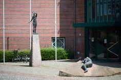 #Ahrensburg Besucher des Amtsgerichtes in Ahrensburg treffen vor dem Betreten des Gebäudes rechts und links des Eingangs auf zwei Figuren. Die eine steht aufrecht und erhöht auf einem schmalen Sockel, die andere liegt mit angewinkelten Beinen auf einem leicht schrägen, flachen und breiten Podest. Auch wenn die Figuren nicht miteinander interagieren und sich nicht ansehen, stehen sie doch miteinander in Beziehung.