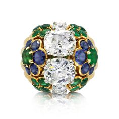 A Cartier diamond cocktail ring is the consummate gift for the glamazon. Designed with two old-mine cut cushion diamonds within calibre-cut emerald and sapphire circular flowerheads mounted in gold 1960's. Weight of diamonds approximately 1.95 carats and 2.13 carats respectively.
