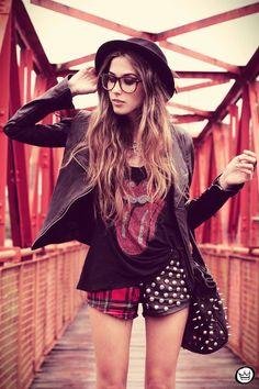 Plaid and Studded Shorts, Rolling Stones Tee Shirt, Black Leather Jacket, Brimmed Hat, Large Glasses, Studded Bag.