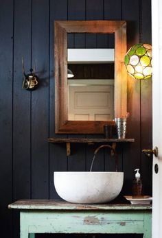 Love the contrast of the old painted table against the new painted wood walls and the unpainted wood mirror. I also love the bright colored lamp.