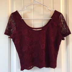 American Rag Crop Top The tag says XL, but it definitely fits more like a large. Very pretty lace details and super super soft material. The color is a garnet or deep red. I've never worn it, as it is too small, so it's in great condition, new without tags American Rag Tops Crop Tops