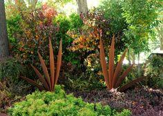 sculptures en acier Corten qui contrastent avec les plantes vertes dans le jardin