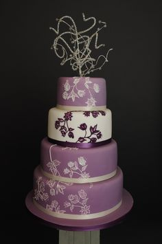 Gorgeous brushed embroidery purple and white four tiered stacked wedding cake. --- maybe top two tiers?