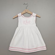 With soft pink ric rac on a crisp white background, this dress is a favorite in our baby girl clothing boutique. It is handmade in the USA with a high waist and covered button closures which creates a classic look for any taste.