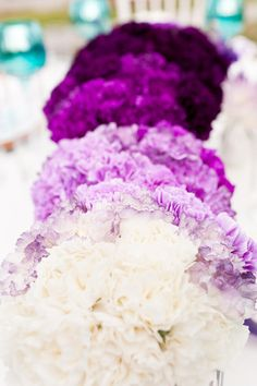 bridesmaids each carry different shades of the same color flowers. I'm IN LOVE with this idea!