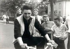 Elvis riding a bicycle on Goethestraße in Bad Nauheim, Germany - 1959. Note the pen for authographs in his right hand. His dentist's house is on the right in the background.