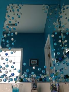 Use Dollar Store glass vase fillers to turn a builders mirror into a beautiful addition to your bathroom. This is an Under the Sea theme kid's bathroom.