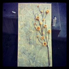 Old book pages modge podged onto canvas with a branch and paper roses