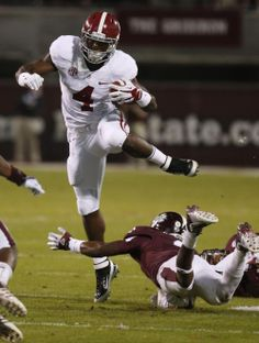 Alabama running back T.J. Yeldon (4) leaps past an attempted tackle by Mississippi State defensive back Will Redmond