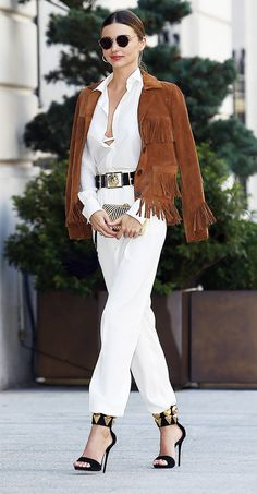 Western jacket draped over all-white attire with black and gold accents. // #StreetStyle #MirandaKerr
