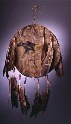 Shield, Plains Indian, 1880s leather, metal, eagle feathers, pigments and wool, 31 x 17 3/4 inches
