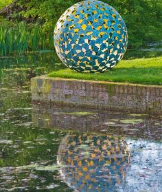 David Harber - Mantle outdoor sculpture with reflection in a lake