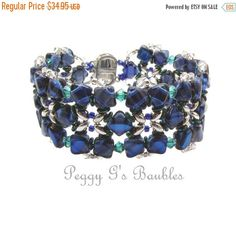 FREE USPS SHIPPING IN THE 50 U.S. STATES!!!  This floral motif bracelet was made with a new Silky bead in the Sapphire Azuro Blue color which is a beautiful deep blue hue. I accented the blue beads with smaller green beads and embellished it on the outer edge with crystal (clear) and emerald green crystals. Sapphire blue and emerald green look so fabulously rich together!! I finished it with a silver filigree snap clasp. This bracelet as shown is 7-1/8 inches in length and 1-1/8 inc...