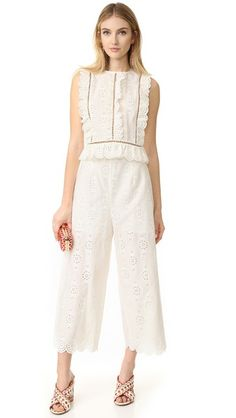 Eyelet ruffles and see-through lattice seams lend charming style to this Zimmermann crop top. Lace-up detailing accents the back. Sleeveless. Hidden zippers at shoulders and at side. Semi-sheer.