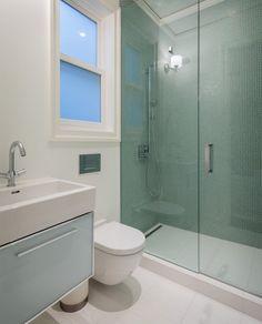 zone douche décorée d'un carrelage vert avec une porte coulissante en verre