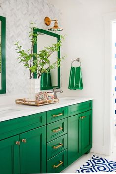 an emerald sink stand and framed mirrors add color to the space and are spruced up with brass touches