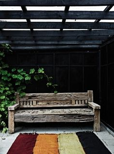 Earthy, worn down bench meets dark background adding a touch of sophistication. And the rug!