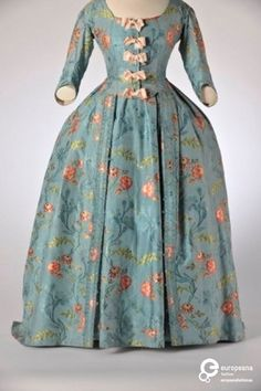 ca 1735, an early robe a la francaiset, with bodice, or caraco, under skirt, and over skirt of matching blue taffeta with multicolored floral embroidery. The bodice with deep square decolletage and matching three-quarter sleeves, with five crossed pink bows. Belgium Modemuseum