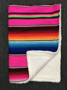 The perfect combination of style and utility. Each blanket is hand made with a Mexican serape blanket on one side and a super soft sherpa material on the other. Great as a baby blanket, stroller blank