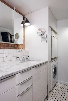 Well designed laundry room with clean modern feel. White walls, black and tile floor tile, and exposed brick.