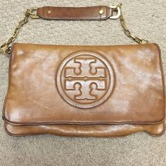 ✨TORY BURCH Bombe Reva Clutch Leather bag! purchased at Neiman Marcus in the Natick mall a few years ago. I haven't worn it in two years, but for a little stretch it got some use, reflected in price. A modern classic iconic clutch in luxurious bombe leather w/ gold hardware. Tory Burch logo adorns the front of the bag.  Flap-front clutch, with two inner pockets - one along top and one in bottom. gold hardware zippers. Gently worn -  pen marks on inside and some fading/natural distress of the…