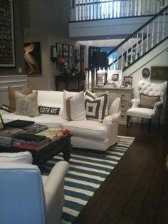 Beach house decor. Dark hardwood floors and furniture, except for white dresser. Dark banister.