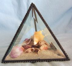 Beach treasures glass pyramid mini beach tropical sand and sea shell executive desk beach display with free stained glass ornament. $28.00, via Etsy.