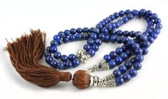 Lapis Mala Bead Necklace - These are beautiful natural beads. The wood Guru Bead is carved into a lotus flower shape, silky tassel is made from bamboo fibre