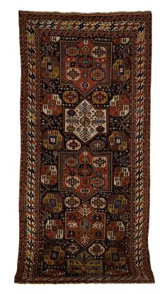 """Kazak long rug, ca. 1910, with repeating medallions on a blue field with running dog border, 13' x 5'8""""."""