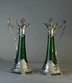 Elaborately adorned, exquisite green glass pitchers exhibit highly detailed and accomplished overlay silver work by WMF.