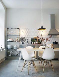 Cozinha estilo industrial com mesa e cadeiras pé palito e piso de cimento queimado
