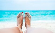 Sandy feet with nail varnish on toes on a beach