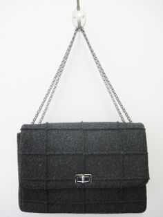 4a251a2faa1f Charcoal grey wool bag in a square quilted pattern with raw edges facing  outward. Features pewter mademoiselle turn lock closure with double chain  straps.