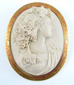 "Bacchante 14k Lava Stone Cameo Brooch: The gorgeous woman portrayed in this cameo is Bacchante, the female follower of Bacchus, the god of wine. Comprised of lava stone, this brooch is carved with amazing detail. This incredible piece is framed with 14k gold etched with a delicate flowing design. Tested 14k, c-clasp, measures 2-3/8"" by 1-7/8""."