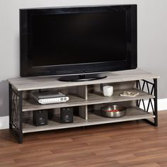 Update your living room with 60-inch TV Stand. X-shaped steel supports add a decorative and sturdy touch, while the grey reclaimed finish adds rustic charm to any home space.