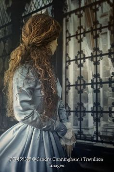 Trevillion Images - historical-woman-in-blue-gown-by-window