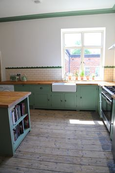 Bespoke, solid wood kitchen finished in Farrow & Ball 'Breakfast Room Green' with double Belfast sink and solid pine worktops.