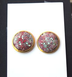 Get in the holiday spirit with these eye-catching red, gold, and green sparkly stud earrings! They arrive ready for giving as a stocking stuffer/ filler or for wearing to your next holiday party.      These round 14mm stud earrings are made of multicolored glitter and glass glitter embedded into epoxy clay and mounted into gold plated post earring settings. Butterfly earring backs are included.     The studs are lead and nickel free.    Arrives packaged in an elegant branded black and white…