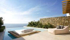 floating sun lounger daybed, honey stone wall and simple planting, large lounging pillow for 2 - Private Villa Mykonos Town | Cavo Tagoo Mykonos Luxury Villas