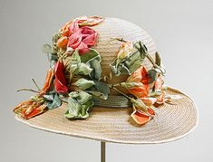 A summery straw cloche decorated with silk flowers, made in Los Angeles between 1925 and 1930.
