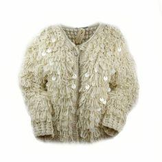 70% acryl 30% wol.  Kort gebreid grof vest met grote lussen.  Tussen de lussen door zitten grote crème kleurige pailletten verwerkt.  Het vest is ongeveer 55 cm lang.  One size fits all.