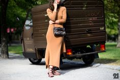Woman in beige dress next to a brown truck